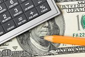 Calculator, money and pencil - business background