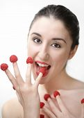 Young sexy woman eating raspberries off fingers