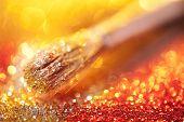 Close-up on makeup brush and gold shining powder
