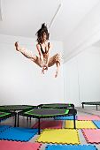 Jumping brunette woman on a trampoline