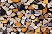 Dry chopped firewood logs in a pile - wood background