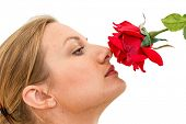 beautiful woman holding red rose and enjoying its smell