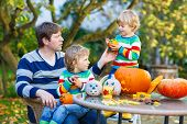 Young Dad And His Little Son Making Jack-o-lantern For Halloween In Autumn Garden