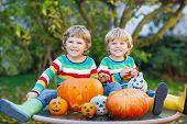 Two Little Friends Boys Making Jack-o-lantern For Halloween In Autumn Garden