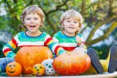 Two Little Kid Boys Making Jack-o-lantern For Halloween In Autumn Garden