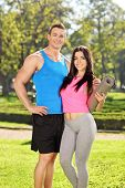 Young couple in sportswear posing in park on a sunny day