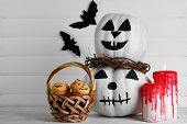 White Halloween pumpkins, candles and candies, on color wooden background