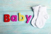 Baby word formed with colorful letters on wooden background