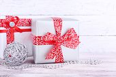 Holiday gift boxes decorated with red ribbon on table on wooden wall background