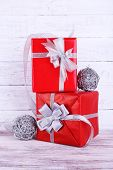 Red holiday gift boxes decorated with ribbon on wooden wall background