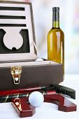 Golf set in suitcase with bottle of wine on table on bright background
