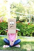 Woman with cardboard box on her head with sad face, outdoors