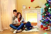 Nice love couple sitting on carpet in front of fireplace. Woman and man celebrating Christmas
