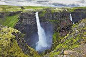 Hayfoss dangerous waterfall in Iceland. Vertical cliff, from which the powerful waterfall flies on black stones