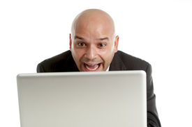 image of spanish money  - young businessman typing on computer keyboard with funny face expression on watching internet porn online or making money gambling on line isolated on white background - JPG