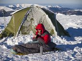 pic of thermos  - A man sits in a sleeping bag near the tent and drinking tea from a thermos on the background of the winter mountains - JPG