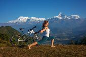 picture of  practices  - woman practicing yoga relaxing after riding bikes high in mountain - JPG
