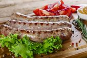 picture of grilled sausage  - grilled sausages on the grill on the board - JPG