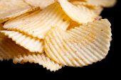 image of crisps  - Ridged fried potato crisps on black surface - JPG