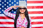 pic of funky  - Beautiful young black woman in funky clothes smiling and gesturing while standing against American flag - JPG