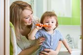 mother teaching kid teeth brushing