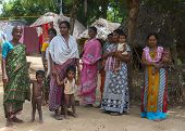 Group Of Women And Babies In Village Setting.
