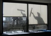 Window washers in silhouette