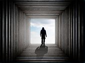 stock photo of underworld  - Silhouette of a man on the edge of the wood tunnel looking down - JPG