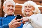 stock photo of bonding  - Happy senior couple bonding to each other and smiling while standing outdoors and looking at the mobile phone - JPG