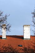 picture of red siding  - Two chimneys on red tiled roof on one of the historic buildings in the center of Prague on the background of bright blue sky - JPG