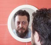 stock photo of beard  - Bearded man preparing to cut his beard with scissors - JPG