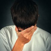 stock photo of sorrow  - Toned Photo of Sorrowful Young Man on the Black Background - JPG