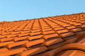 foto of red roof tile  - Red tile roof closeup on blue sky background - JPG