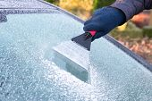 foto of ice-scraper  - Hand with ice scraper removing ice from car windshield - JPG