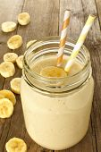 stock photo of masonic  - Banana oatmeal breakfast smoothie in mason jar on wood table - JPG