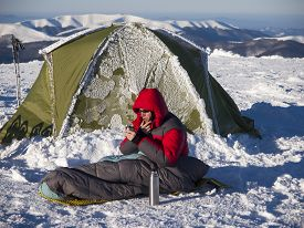 foto of thermos  - A man sits in a sleeping bag near the tent and drinking tea from a thermos on the background of the winter mountains - JPG
