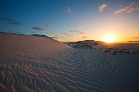 stock photo of glorious  - Glorious sunset over a rippled sand dune next to a lagoon - JPG