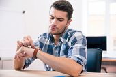 pic of wrist  - Handsome young businessman in casual cloth looking on wrist watch - JPG