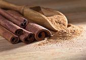 foto of cinnamon sticks  - cinnamon sticks and powder on a wooden table - JPG