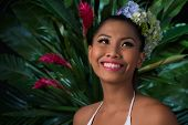 stock photo of filipina  - Beautiful young woman with flowers in her hair smiling and looking up - JPG