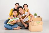 picture of family bonding  - Bonding Asian family sitting on the floor in their new house - JPG