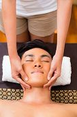 image of massage oil  - Indonesian Asian man in wellness beauty spa having aroma therapy face massage with essential oil - JPG