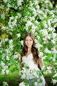 stock photo of allergies  - Young spring fashion woman in spring garden Springtime Summertime Trendy girl in the flowering trees in then at sunset in spring summer landscape background Allergic to pollen of flowers Allergy  - JPG