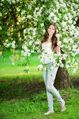 stock photo of allergy  - Young spring fashion woman in spring garden Springtime Summertime Trendy girl in the flowering trees in then at sunset in spring summer landscape background Allergic to pollen of flowers Allergy  - JPG