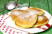 stock photo of sugar  - Traditional Russian fritter with powdered sugar on a plate with sieve with powdered sugar on a green wooden table - JPG