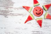 stock photo of watermelon slices  - watermelon slices arranged in a corner decoration on a wooden plank background with copyspace for your text - JPG