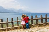 stock photo of wooden fence  - Two cute kids near wooden fence seeing on the seascape - JPG
