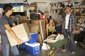 stock photo of yard sale  - Teenage Family Clearing Garage For Yard Sale - JPG