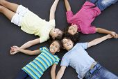 foto of 11 year old  - Overhead View Of Group Of Children Lying On Trampoline Together - JPG
