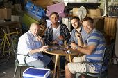 stock photo of garage  - Group Of Male Friends Playing Cards In Garage - JPG